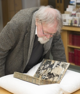 Artist and writer Alasdair Gray viewing one of Edwin Morgan's scrapbooks.