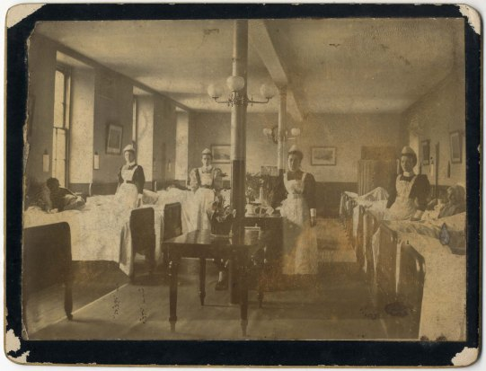 Black and white photograph of 4 nurses standing beside 2 rows of beds in hospital ward.