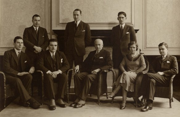 Black and white photograph of 7 men and 1 woman in a formal posed group