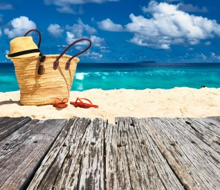 A beach with a beach bag, flip flops, and a sun hat.